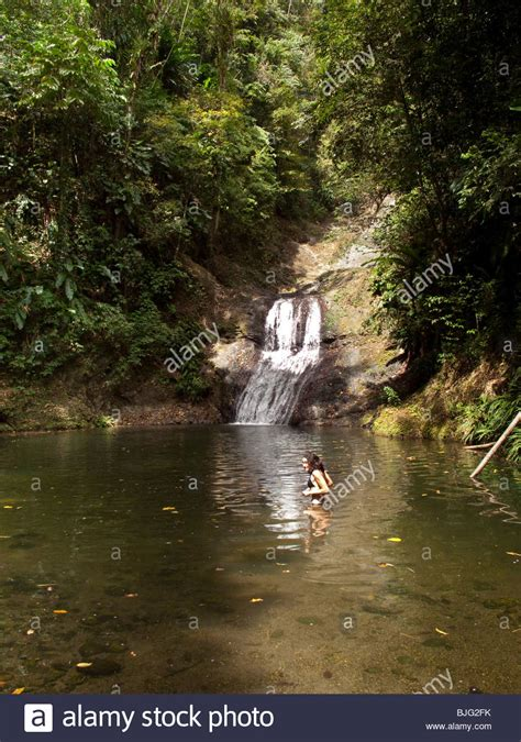 Girl bathing in river near waterfall situated in Caribbean